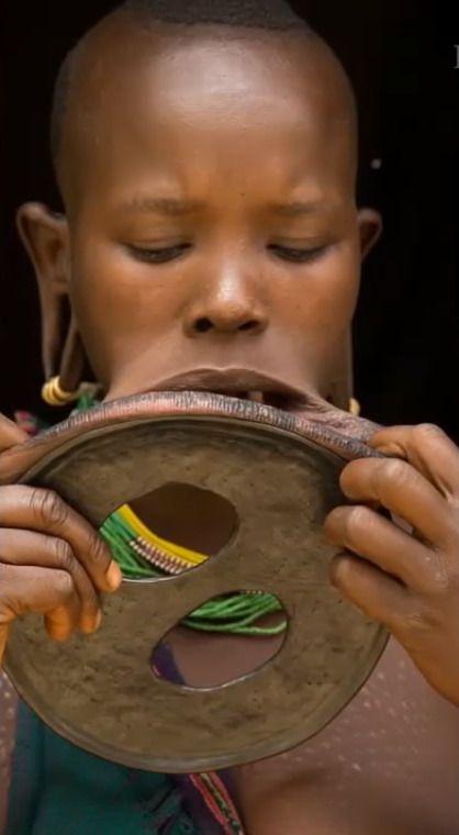 Эта Эфиопка вошла в книгу рекордов Гиннеса за самый большой диск, который она носит в губе. Её невероятно большие губы обхватывают диск размером 59,5 см в окружности и 19,5 см в диаметре, что в два раза больше среднего размера диска, который носят Эфиопы.  Она была обнаружена австралийскими телевизионщиками, когда те делали документальный фильм об Эфиопии.  Они снимали сюжет в отдаленных долинах Южной Эфиопии, когда увидели эту девушку из племени. Звали её Атайя, и диск в её губе был даже больше, чем её голова. Съемочная группа была поражена, но не меньше удивлялись и местные жители своей землячке, которые видели её впервые.  Съемочная группа узнала, что девушке потребовалось три года, чтобы её губа стала такого размера. Кроме того, ей удалили нижние зубы, чтобы диски могли встать на место.  Ребята поделились с девушкой кока-колой, и, на удивление, она выпила её, просто вылив на язык. «Это было ошеломительно», — вспоминают они.  Ношение таких украшений считается в Эфиопии символом красоты и достатка. И, чем больше эти диски — тем больше семья невесты получит во время свадебного выкупа.  Так что эта девушка завидная невеста!  Обычно эта процедура выполняется для девушек возраста 15-18 лет.  Судя по всему, Атайе есть, чем гордиться.